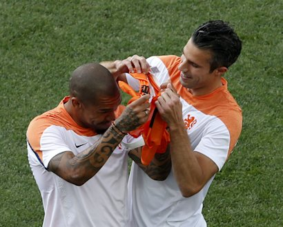 Netherlands' national soccer player Robin Van Persie (R) jokes with his teammate Wesley Sneijde during their 2014 World Cup training session at the Co...