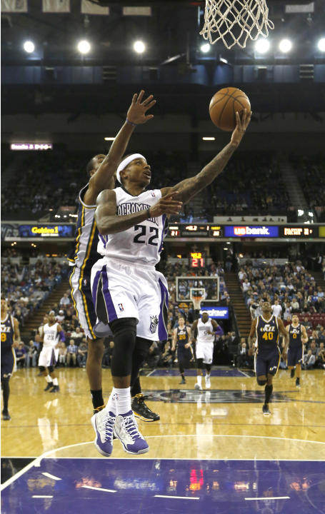 Sacramento Kings guard Isaiah Thomas, right drives to the basket past Utah Jazz Alec Burks during the first quarter of an NBA basketball game in Sacramento, Calif., Wednesday, Dec. 11, 2013
