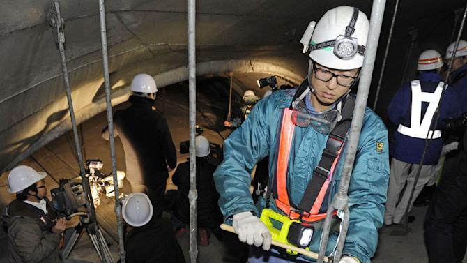 Workers inspect the structure inside the 1.65-kilometer (1-mile) Tsuburano Tunnel on the Tomei Expressway in Yamakitamachi, Kanagawa Prefecture, eastern Japan, Monday, Dec. 3, 2012. Concrete ceiling panels fell onto moving vehicles deep inside a tunnel on another expressway in Japan Sunday, and authorities confirmed nine deaths before suspending rescue work Monday while the roof was being reinforced to prevent more collapses. (AP Photo/Kyodo News) JAPAN OUT, MANDATORY CREDIT, NO LICENSING IN CHINA, FRANCE, HONG KONG, JAPAN AND SOUTH KOREA