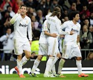 Real Madrid's Cristiano Ronaldo (L) celebrates after scoring their second goal during the Spanish La Liga match vs Sporting Gijon, at the Santiago Barnabeu stadium in Madrid, on April 14. Real travel to Barcelona next, on Saturday, for the sixth 'Clasico' of the season