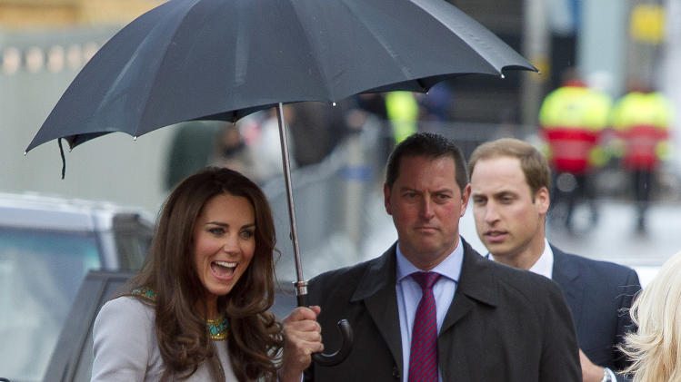 The Duchess of Cambridge, left, arrives under an umbrella for the UK Premiere of 'African Cats', in aid of  'Tusk Trust', at the BFI Southbank  in central London, Wednesday, April 25, 2012. (AP Photo/Joel Ryan)