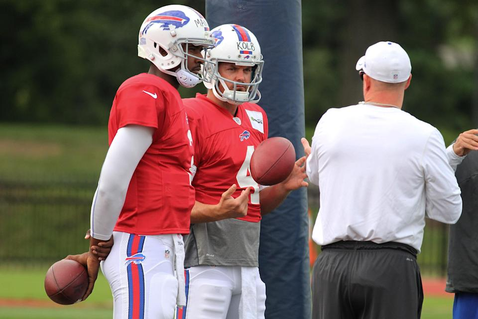 Buffalo Bills quarterbacks EJ Manuel (3) and Kevin Kolb (4) talk to offensive coordinator Nathaniel Hackett during their NFL football training camp in Pittsford, N.Y., Tuesday, July 30, 2013. (AP Photo/Bill Wippert)