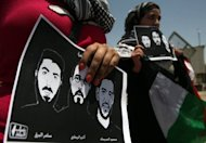 Female protesters hold pictures of jailed Palestinian prisoners during a demonstration in front of Ofer prison, near the city of Ramallah