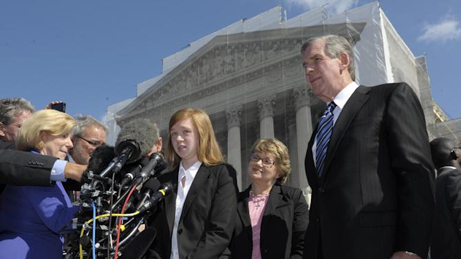 Abigail Fisher, the Texan involved in the University of Texas affirmative action case, accompanied by her attorney Bert Rein, right, talks to reporters outside the Supreme Court in Washington, Wednesday, Oct. 10, 2012. The Supreme Court is taking up a challenge to a University of Texas program that considers race in some college admissions. The case could produce new limits on affirmative action at universities, or roll it back entirely. The University of Texas at Austin President Bill Powers is at right.(AP Photo/Susan Walsh)