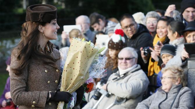 Britain's Catherine, Duchess of Cambridge carries flowers as she leaves a Christmas Day morning service at the church on the Sandringham Estate in Norfolk, eastern England