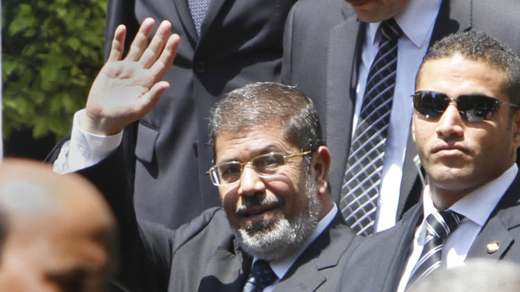 """Egyptian President Mohammed Morsi waves to photographers as he leaves the Arab League headquarters in Cairo, Egypt, Wednesday, Sept. 5, 2012. Morsi says Syrian leader Bashar Assad must learn from """"recent history"""" and step down before it is too late. (AP Photo/Amr Nabil)"""