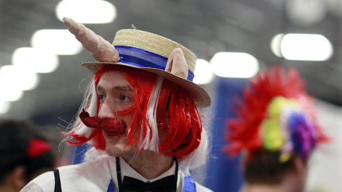 "Josiah Tyrrell, of Syracuse, N.Y., is dressed as the character Flam from the My Little Pony cartoons as he stands with others at ""BronyCon"" Saturday, June, 30, 2012, in Secaucus, N.J. Scores of men in brightly colored costumes were among the 4,000 My Little Pony fans at this weekend's ""BronyCon"" gathering in New Jersey for fans of a My Little Pony cartoon.  (AP Photo/Mel Evans)"