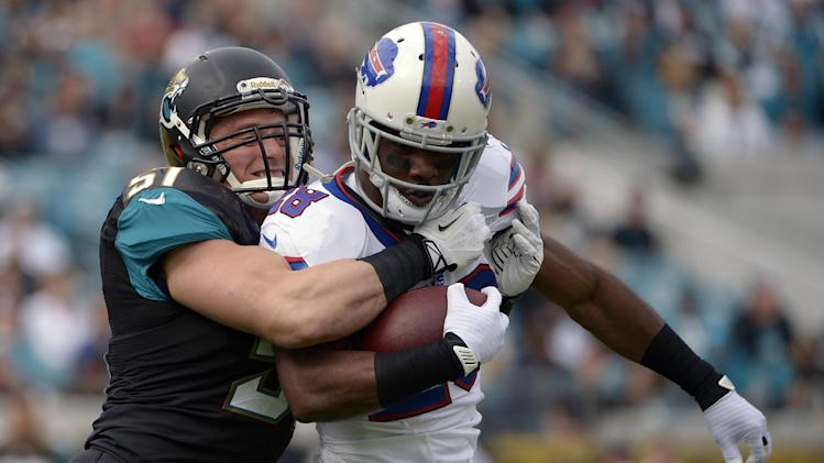 CORRECTS PHOTOGRAPHER TO PHELAN M. EBENHACK FROM JOHN RAOUX - Jacksonville Jaguars middle linebacker Paul Posluszny (51) stops Buffalo Bills running back C.J. Spiller after a short gain during the first half of an NFL football game in Jacksonville, Fla., Sunday, Dec. 15, 2013