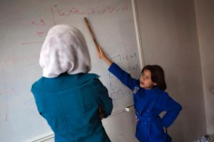 A Syrian student shows a word on a whiteboard during …