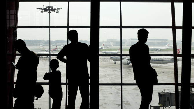 In this Thursday Aug. 1, 2013 photo, passengers look out of the window while airliners line up near a runway at Terminal 3 of Beijing International Airport in Beijing, China. China's fast growing air travel market is the world's second biggest. But when it comes to flight delays, it's No. 1. According to official figures, 75 percent of China's flights left on time last year. But private surveys paint a different picture. A recent report by travel industry monitor FlighStat Inc. found that just 18 percent of flights at Beijing's airport left on time in June, the lowest proportion among 35 airports worldwide, with Shanghai second at 29 percent. Eight of the 10 worst performing airlines were mainland Chinese carriers. (AP Photo/Alexander F. Yuan)