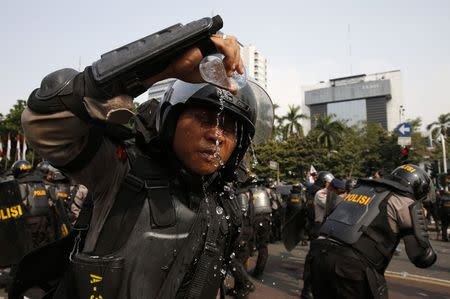An Indonesian police officer washes his face from the effects of tear gas during a protest near the Constitutional Court in Jakarta