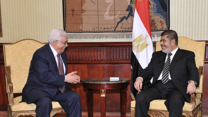 In this photo released by the Egyptian Presidency, Palestinian President Mahmoud Abbas, left, laughs with Egyptian President Mohammed Morsi during a photo opportunity following Abbas' arrival in Cairo, Egypt, for the Organization of Islamic Cooperation summit, Tuesday, Feb. 5, 2013. (AP Photo/Egyptian Presidency)