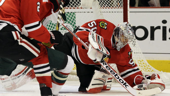 Chicago Blackhawks goalie Corey Crawford, right, saves a shot by Minnesota Wild's Charlie Coyle (not shown) during the first period of Game 2 of an NHL hockey Stanley Cup first-round playoff series in Chicago, Friday, May 3, 2013. (AP Photo/Nam Y. Huh)