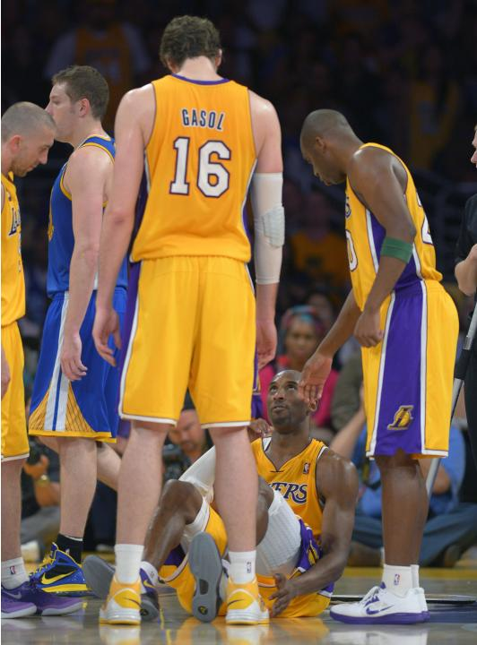 Los Angeles Lakers guard Kobe Bryant, second from right, looks up sat Pau Gasol, of Spain, and guard Jodie Meeks, right, after being injured during the second half of their NBA basketball game against