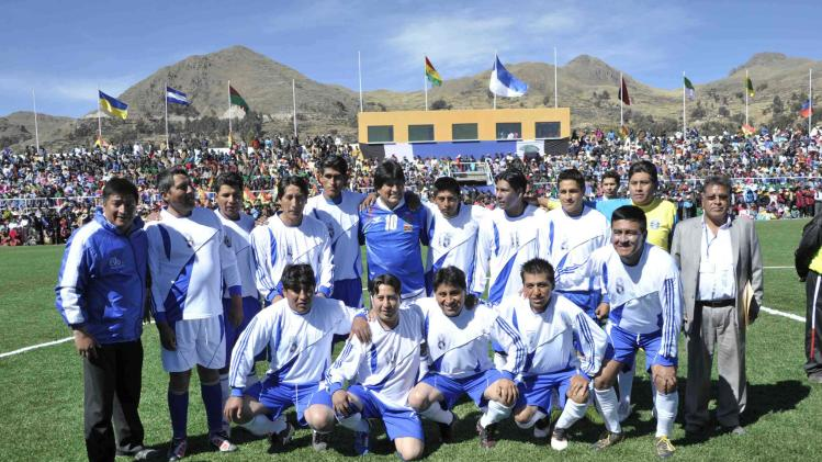 Handout photo shows Bolivia's President Evo Morales posing with the Copacabana residents team before a friendly match, at the inauguration of a sport field at Lake Titicaca in Copacabana