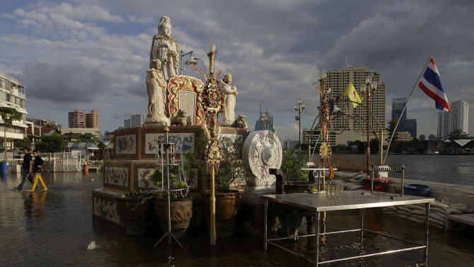 Thai residents walk along a flooded area at the Phothisathan Mokholthan temple beside the swollen Chao Phraya River in Bangkok, Thailand, Saturday, Oct. 29, 2011. The complex network of flood defenses erected to shield Thailand's capital from the country's worst floods in nearly 60 years was put to the test Saturday as coastal high tides hit their peak. (AP Photo/Aaron Favila)