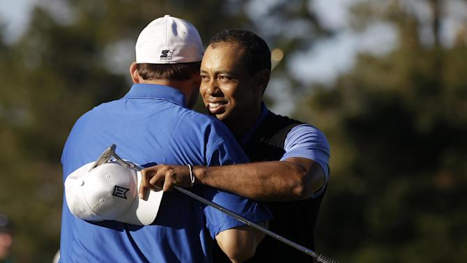 Tiger Woods, right, hugs his amateur partner, Dallas Cowboys quarterback Tony Romo, after finishing on the ninth hole at Spyglass Hill Golf Course during the first round of the AT&T Pebble Beach National Pro-Am golf tournament in Pebble Beach, Calif., Thursday, Feb. 9, 2012. (AP Photo/Marcio Jose Sanchez)