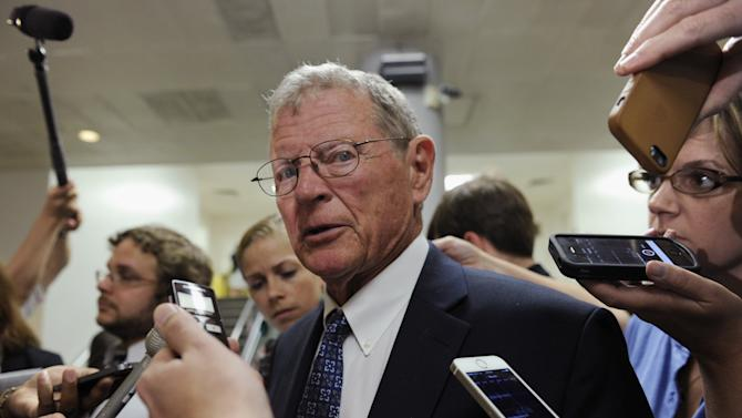 """FILE - in this July 8, 2014, file photo, Sen. James Inhofe, R-Okla., speaks to reporters on Capitol Hill in Washington. Inhofe, who will take over the Senate Environment and Public Works Committee in January, said in a statement late Tuesday, Nov. 25, 2104, that a stricter standard to be announced Wednesday by the Obama administration on smog-forming pollution allowed in the air """"will lower our nation's economic competitiveness and stifle job creation for decades."""" He vowed """"vigorous oversight"""" of the proposal in his new position. (AP Photo/Susan Walsh)"""