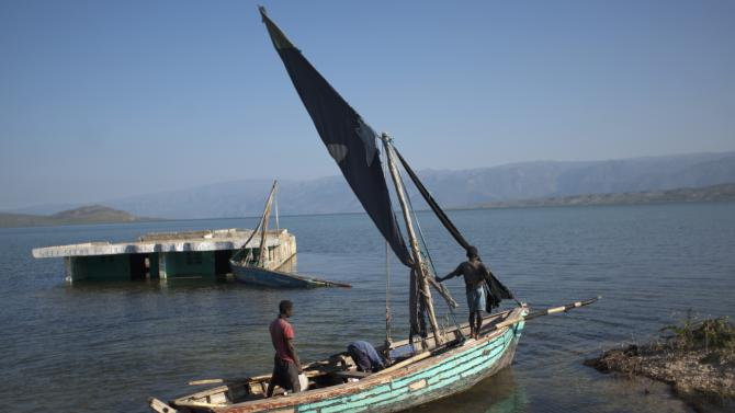 In this Sept. 5, 2012 photo, youths clean a boat near a home submerged in Lake Azuei in Malpasse, Haiti, near the border with the Dominican Republic. The waters' rise has worsened exponentially in recent years, especially after heavy rains in 2007 and 2008 hit the island of Hispaniola. Tropical Storm Isaac dumped more water on the region last month, sparking more damage. (AP Photo/Dieu Nalio Chery)