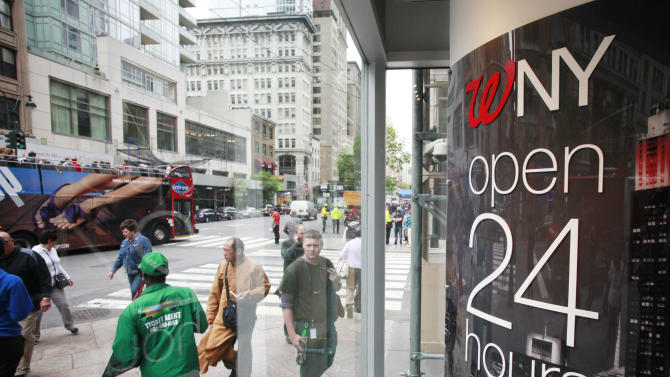 In this Wednesday, May 15, 2013 photo, pedestrians walk in and out of the Walgreens flagship store in the Empire State Building, in New York. The private Conference Board reports on consumer confidence for June, on Tuesday, June 25, 2013. (AP Photo/Mark Lennihan)