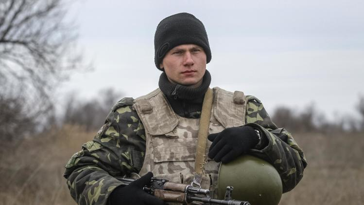 Ukrainian serviceman guards a checkpoint near the village of Strelkovo