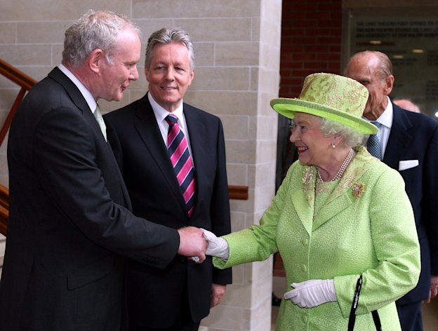 Britain's Queen Elizabeth II shakes hands with Northern Ireland Deputy First Minister and former IRA commander Martin McGuinness watched by First minister Peter Robinson, centre, at the Lyric Theatre in Belfast, Northern Ireland, Wednesday, June 27, 2012. (AP Photo/Paul Faith/pool)