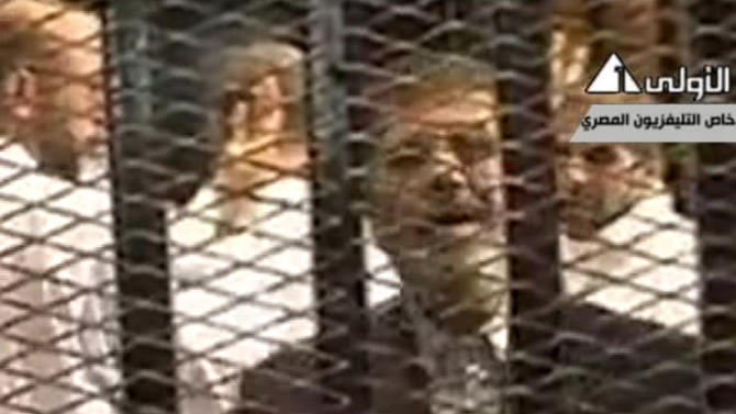 "This image made from video broadcast on Egyptian State Television shows ousted President Mohammed Morsi speaking from inside a mesh cage as he stands with other defendants during a court hearing at a police academy compound in Cairo, Egypt, Monday, Nov. 4, 2013. After four months in secret detention, Egypt's deposed Islamist president defiantly rejected a court's authority to try him Monday, saying he was the country's ""legitimate"" leader and those that overthrew him should face charges instead. The trial was then adjourned until Jan. 8 after several interruptions.(AP Photo/Egyptian State Television via AP video)"