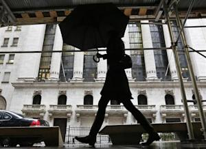 A woman walks past the New York Stock Exchange in New York's financial district