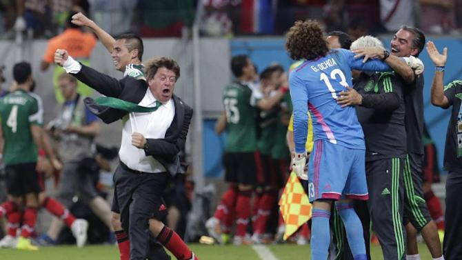 Mexico's head coach Miguel Herrera celebrates after Mexico's Andres Guardado  scored his side's second goal during the group A World Cup soccer match between Croatia and Mexico at the Arena Pernambuco in Recife, Brazil, Monday, June 23, 2014