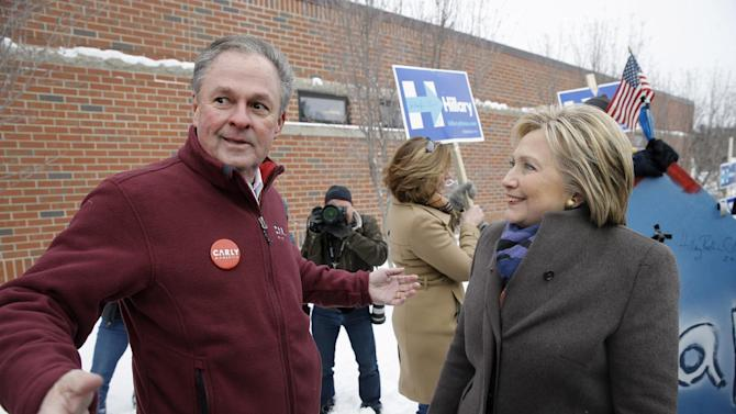 Democratic presidential candidate Hillary Clinton speaks with Frank Fiorina, husband of Republican presidential candidate Carly Fiorina, as they campaign outside a polling place during the first-in-the-nation presidential primary, Tuesday, Feb. 9, 2016, in Derry, N.H. (AP Photo/Matt Rourke)