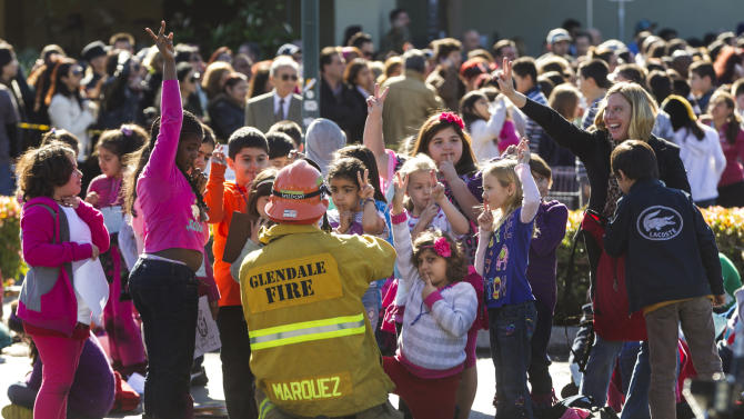 A Glendale fireman talks to elementary school children as they wait to reunite with their parents after their school was evacuated for a bomb threat in Glendale, Calif., Monday, Jan. 7, 2013. The bomb threat prompted the evacuation of hundreds of children from R.D. White Elementary School on Monday while police searched buildings to make sure the campus was safe. An anonymous caller phoned the school at around 8:30 a.m., and said there was a bomb at the campus, according to police Sgt. Tom Lorenz. (AP Photo/Damian Dovarganes)
