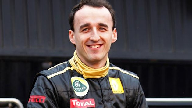 Lotus Renault GP driver Robert Kubica of Poland sits on the tyre of the R31 2011 Formula one car during their team presentation at the Ricardo Tormo racetrack in Cheste, near Valencia, January 31, 2011