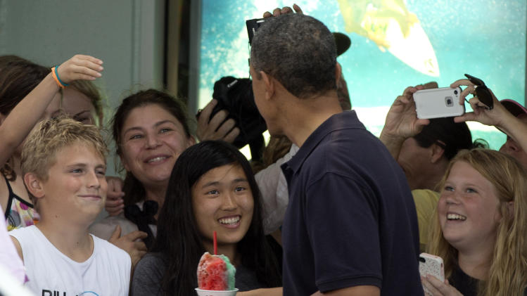 President Barack Obama holds his shave ice as he greets people outside Island Snow, Thursday, Jan. 3, 2013, in Kailua, Hawaii. President Obama and the first family are in Hawaii for a holiday vacation. (AP Photo/Carolyn Kaster)