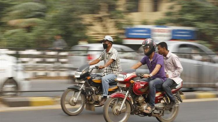 Men ride a TVS Victor (R) motorcycle through a road in Guwahati April 8, 2013. REUTERS/Utpal Baruah/Files