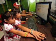 Indonesian children log on a Facebook page at an internet shop in Kuta in the resort island of Bali in February 2012. Facebook is working on technology that would permit children under the age of 13 to use the social network site with parental supervision, people familiar with the effort said
