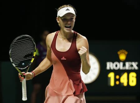 Caroline Wozniacki of Denmark celebrates her win over Agnieszka Radwanska of Poland during WTA Finals singles tennis match at the Singapore Indoor Stadium
