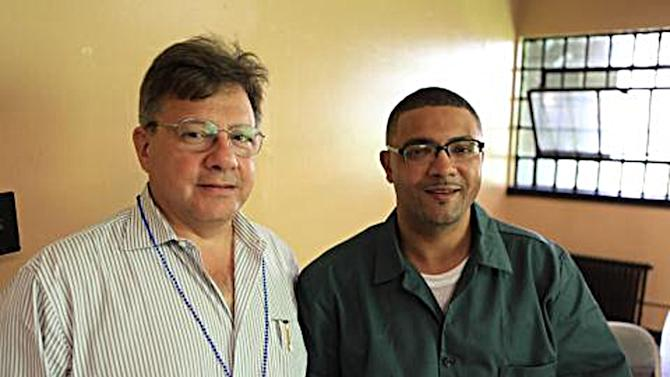This Wednesday, Aug. 1, 2012 photo provided by attorney Peter Cross shows Cross, left, posing while on a visit with his client Eric Glisson at New York's Sing Sing prison. Glisson was convicted in the 1995 killing of a livery cab driver in New York City but a review of new evidence points to a wrongful murder conviction. (AP Photo/Peter Cross)