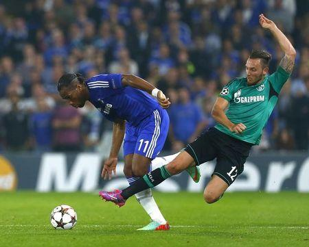 Chelsea's Drogba is challenged by Schalke 04's Hoger during their Champions League soccer match at Stamford Bridge in London