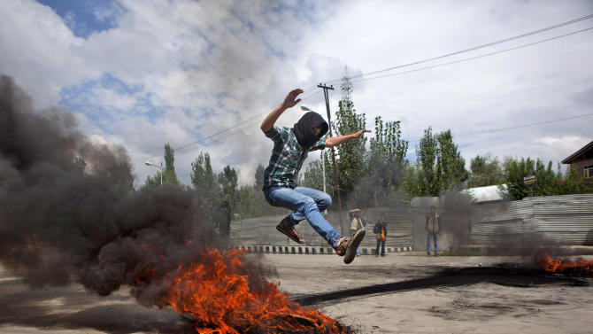 A Kashmiri Muslim protester jumps over a burning tire set up as a road block during a protest in Srinagar, India, Tuesday, Sept. 18, 2012, as part of widespread anger across the Muslim world about a film ridiculing Islam's Prophet Muhammad. (AP Photo/ Dar Yasin)