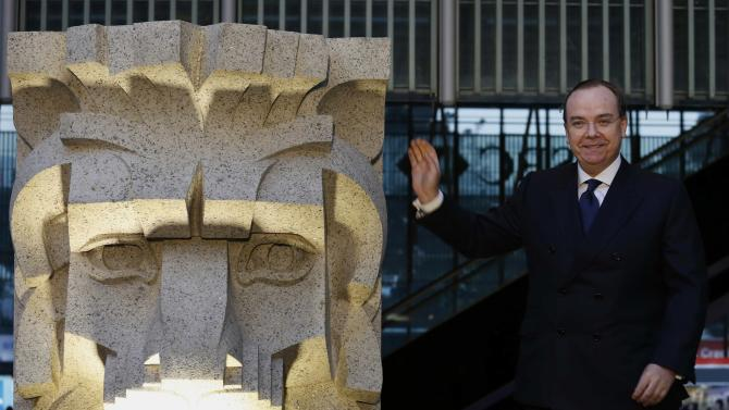 HSBC Group Chief Executive Gulliver gestures beside a lion sculpture during a main building plaza reopening ceremony at HSBC headquarters in Hong Kong
