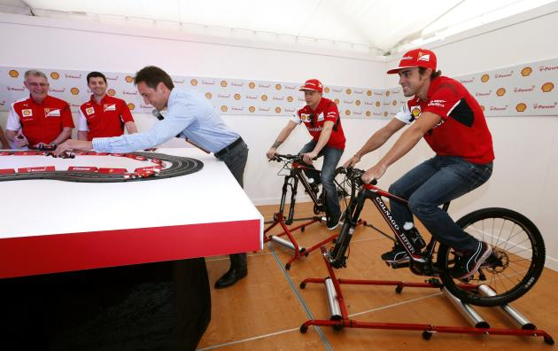 Ferrari Formula One drivers Alonso of Spain and Raikkonen of Finland ride bikes as a presenter adjusts a toy electric car at the premiere of the film 'Horse Power' in Melbourne