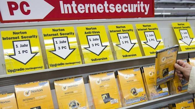 Man takes box of internet security software from shelf at electronic retailer in Berlin