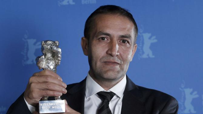"""Actor Nazif Mujic poses backstage with his Silver Bear award for Best Actor for the movie """"An Episode in the Life of an Iron Picker"""" during the awards ceremony at the 63rd Berlinale International Film Festival in Berlin Saturday, Feb. 16, 2013. (AP Photo/Thomas Peter, pool)"""