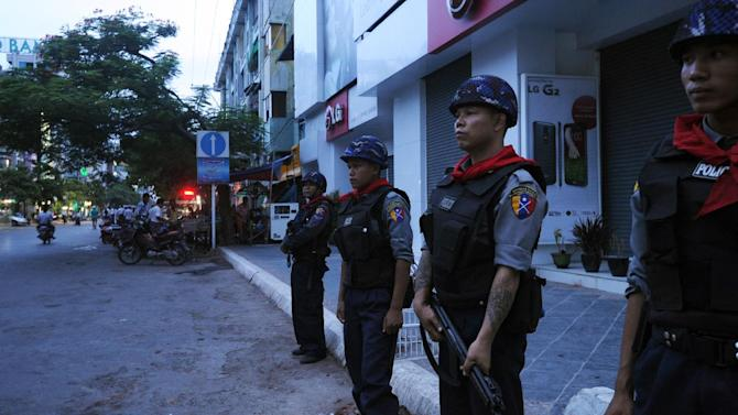 Myanmar police stand guard on a street in Mandalay after deadly Buddhist-Muslim clashes that raised fears of spreading unrest on July 3, 2014