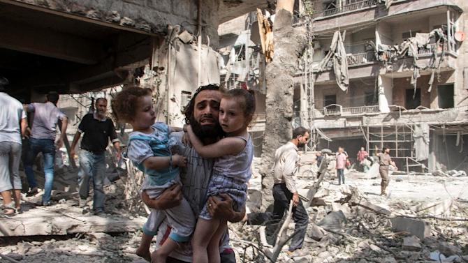 A Syrian man carries two girls through the rubble following a barrel bomb attack on the rebel-held neighbourhood of al-Kalasa in the northern Syrian city of Aleppo on September 17, 2015