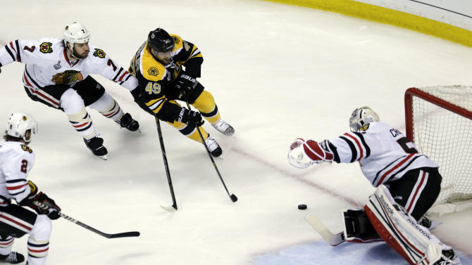 Boston Bruins center Rich Peverley (49) drives to the net against Chicago Blackhawks goalie Corey Crawford, right, as Chicago Blackhawks defensemen Brent Seabrook (7) and Duncan Keith (2) defend during the first period in Game 3 of the NHL hockey Stanley Cup Finals in Boston, Monday, June 17, 2013. (AP Photo/Charles Krupa)