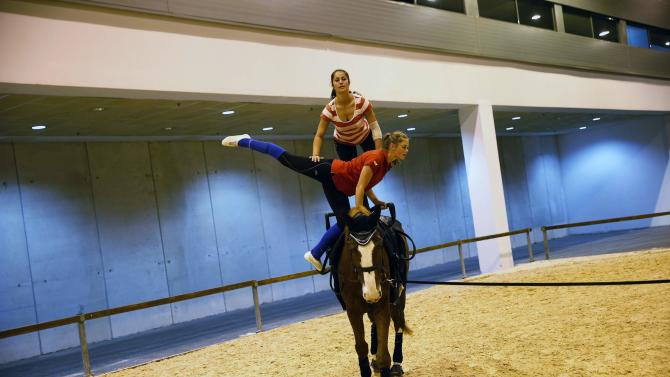 Young women practice vaulting during Madrid Horse Week in Madrid