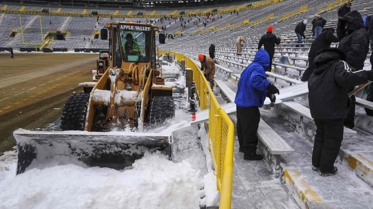 A tractor collects snow which was cleared from the bleachers by paid volunteers at Lambeau Field in Green Bay, Wisconsin