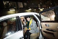 Fashionistas bundle into a car after leaving the Rag & Bone Fall 2013 fashion collection show during Fashion Week, Friday, Feb. 8, 2013, in New York. Snow began falling across the Northeast on Friday, ushering in what was predicted to be a huge, possibly historic blizzard and sending residents scurrying to stock up on food and gas up their cars. (AP Photo/John Minchillo)