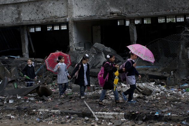 Palestinian schoolchildren walk in debris by a damaged school in Gaza City, Saturday, Nov. 24, 2012. Schools in Gaza opened Saturday for the first time since the truce, which calls for an end to Gaza rocket fire on Israel and Israeli airstrikes on Gaza, came after eight days of cross-border fighting, the bloodiest between Israel and Hamas in four years. The school was damaged when Israeli forces struck on a nearby building. (AP Photo/Bernat Armangue)